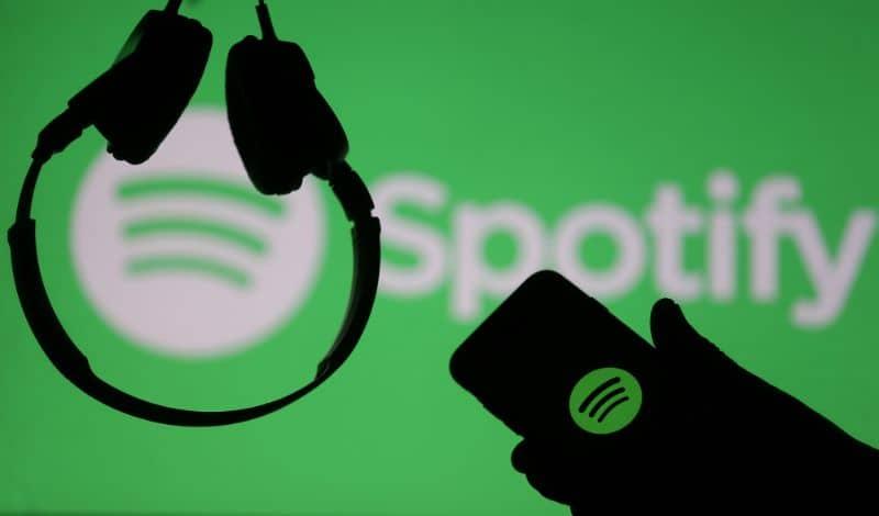 Logo Spotify Cuffie e cellulare in mano