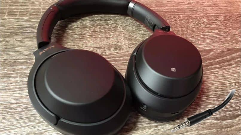 auriculares negros mesa madera cable