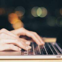 pessoa com as mãos no laptop