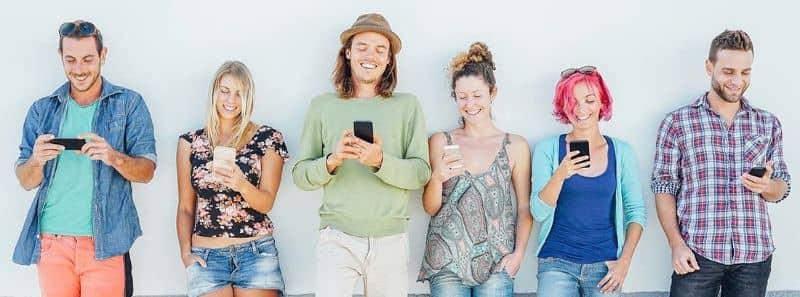 Pessoas sorridentes com dispositivos móveis nas mãos