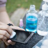 Pessoa que limpa a tela do celular Android com álcool etílico